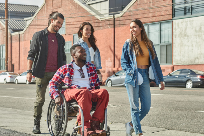 diverse-people-walking-with-disabled-man-on-street